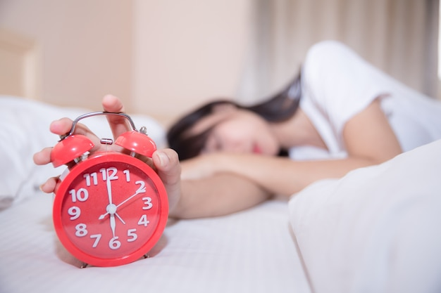 Young sleeping woman and alarm clock in bedroom at home Free Photo