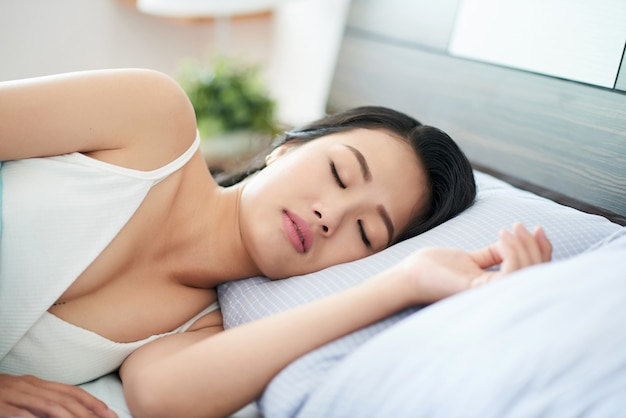 Young sleeping woman on bed Free Photo