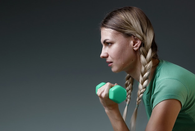Young slender girl works with small dumbbells performing exercises. concept of a healthy lifestyle. gray background. studio light Premium Photo