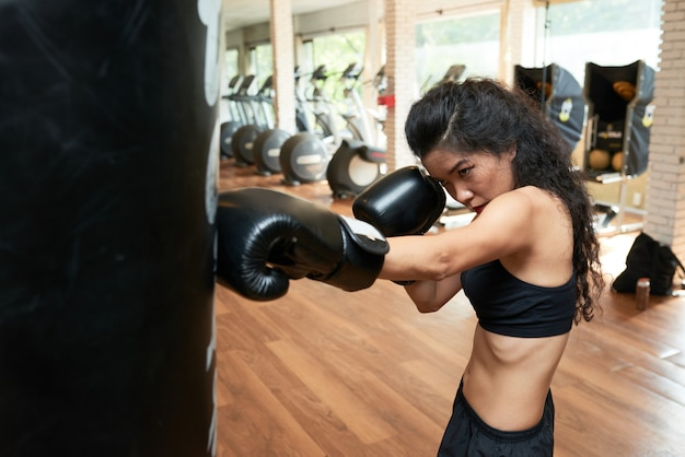 Young slender woman exercising with punching ball in gym Free Photo