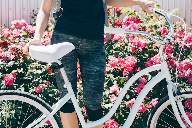 Young slender woman stands with a bicycle against a background of bushes with roses Premium Photo
