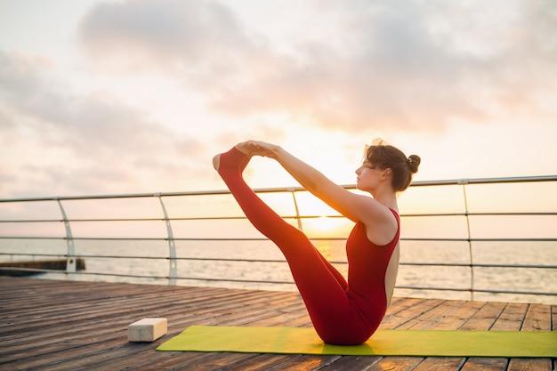Молодая стройная красивая привлекательная женщина занимается йогой по утрам на рассвете у моря, здоровый образ жизни Бесплатные Фотографии