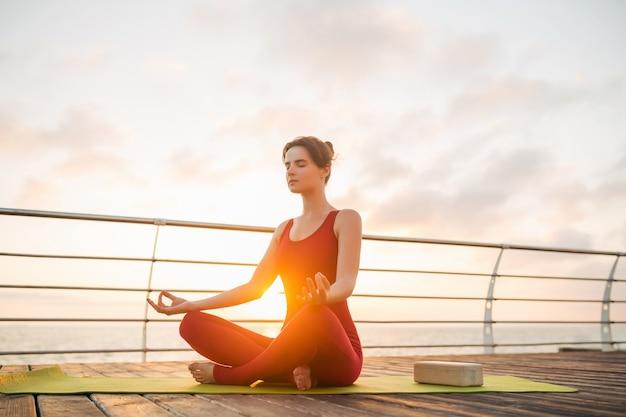 Молодая стройная красивая привлекательная женщина занимается йогой утром на восходе солнца у моря, здоровый образ жизни Бесплатные Фотографии