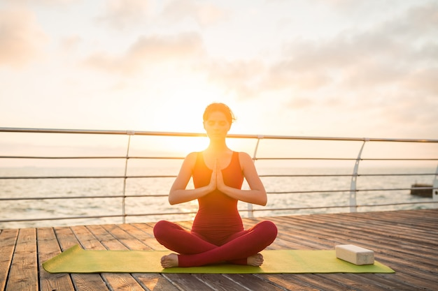 Young slim beautiful attractive woman doing yoga in the morning on sunrise by sea, healthy lifestyle Free Photo