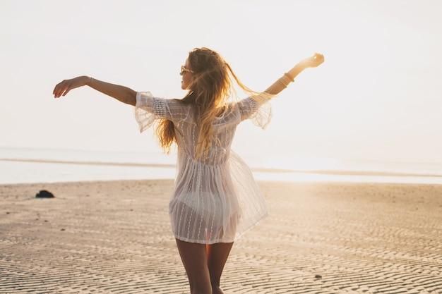 サンセットビーチの若いスリムな美しい女性 無料写真
