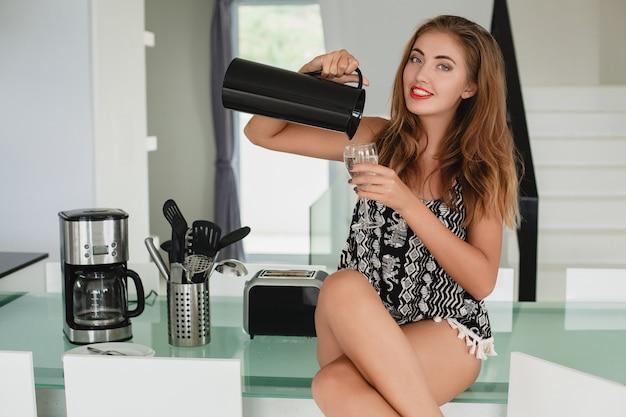 キッチンに座っている若いスリムな美しい女性 無料写真
