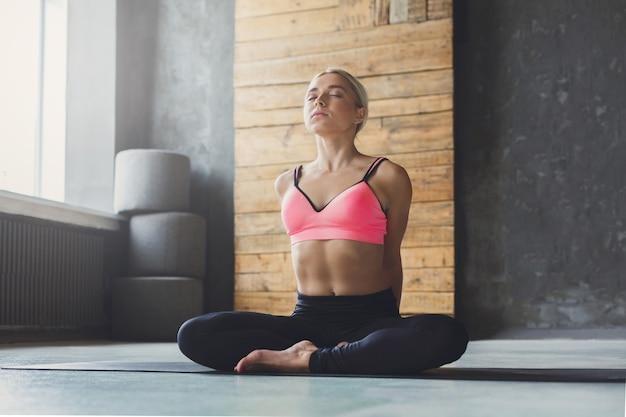 Молодая стройная блондинка женщина в классе йоги, делая упражнения асаны. девушка делает позу полулотоса и растягивает спину. здоровый образ жизни в фитнес-клубе. Premium Фотографии