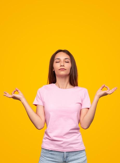 젊은 슬림 여성 Gyan Mudra 몸짓과 노란색 배경에 대해 명상하는 동안 닫힌 눈으로 호흡 프리미엄 사진