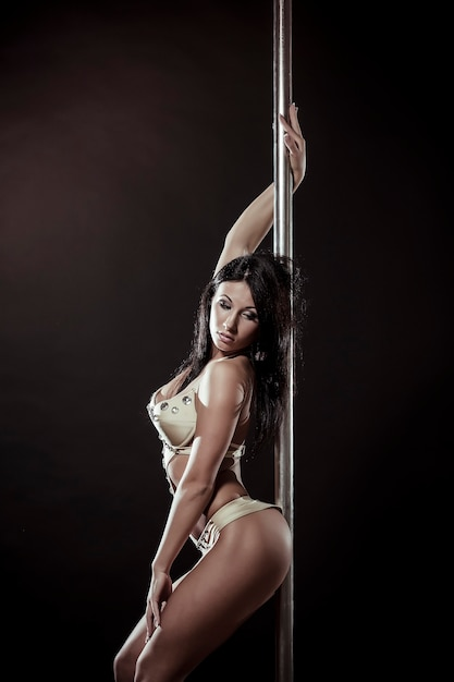 Young slim pole dance woman on a black studio background Free Photo