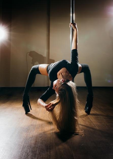 Premium Photo   Young slim sexy woman pole dancing on dark