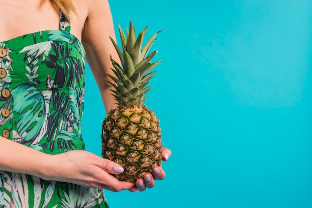 Young slim woman in flowered dress holding pineapple Free Photo