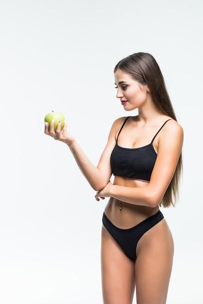 Молодая стройная женщина, держащая зеленое яблоко. изолированные на белой стене. концепция здорового питания и контроль избыточного веса. Бесплатные Фотографии