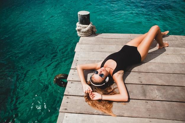 Молодая стройная женщина, лежащая на пирсе, средиземное море, лазурная вода, солнечная, загорелая кожа, слушающая музыка, наушники, черный купальник, сексуальное тело, солнечные ванны, тропический отдых, расслабленный, солнцезащитные очки Бесплатные Фотографии