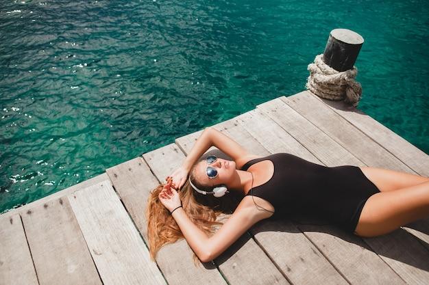 Giovane donna esile che pone sul molo, mar mediterraneo, acqua azzurra, sole, pelle abbronzata, ascolto di musica, cuffie, costume da bagno nero, corpo sexy, prendere il sole, vacanza tropicale, rilassato, occhiali da sole Foto Gratuite