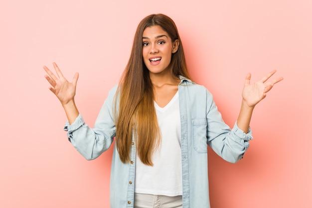 楽しい驚きを受けて、興奮して手を上げる若いスリムな女性。 Premium写真