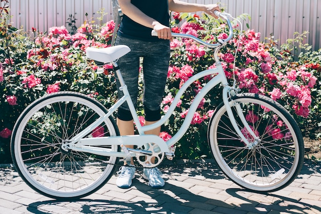Young slim woman standing with bicycle on a background of bushes with roses Premium Photo