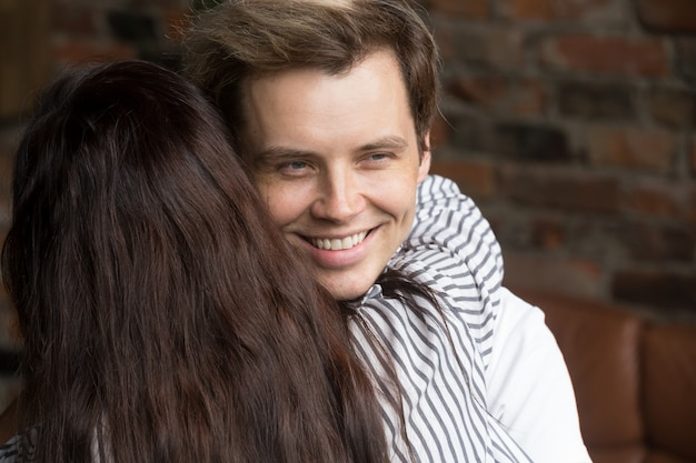 Young sly liar man happily smiling while woman embracing him Free Photo