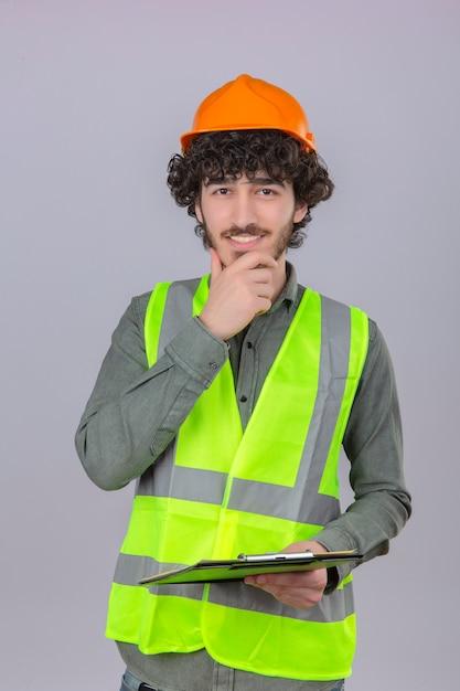 Молодой умный выглядящий панированный красивый инженер-рабочий трогает его подбородок, улыбаясь, стоя на изолированном белом фоне Бесплатные Фотографии