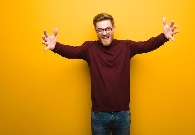 Молодой умный человек очень счастлив, обнимая перед Premium Фотографии