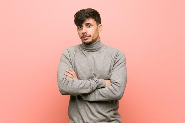 Молодой умный студент человек недоволен, глядя с саркастическим выражением лица. Premium Фотографии