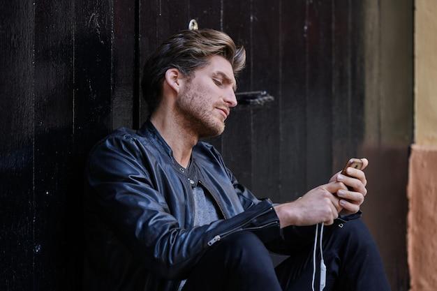 Young smartphone man sitting street Premium Photo