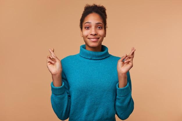 Молодая улыбающаяся афро-американская девушка с вьющимися темными волосами в синем свитере. улыбается, скрестив пальцы и надеется на удачу. изолированные на фоне biege. Бесплатные Фотографии