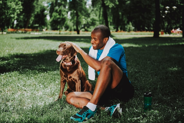 Young smiling african american man petting dog. Premium Photo