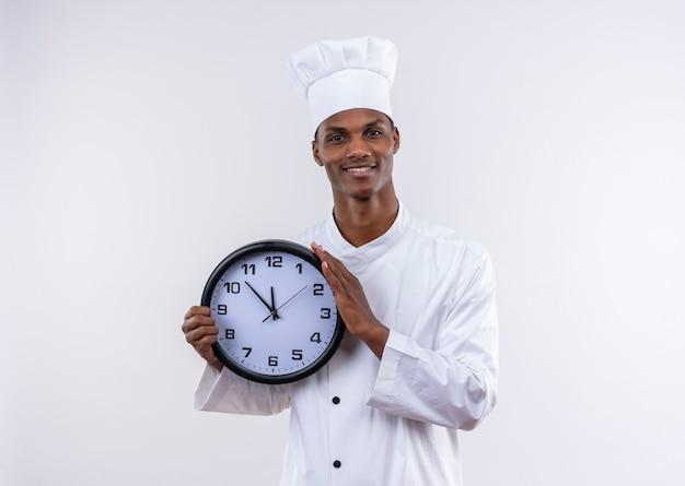 Il giovane cuoco afroamericano sorridente in uniforme del cuoco unico tiene l'orologio isolato sulla parete bianca Foto Gratuite