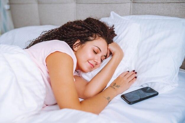 若い笑顔のアフロヘアーの女性は、スマートフォンを閉じてベッドで寝ています。ソーシャルメディア中毒、睡眠モニタリング。 Premium写真