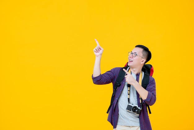 Young smiling asian  male backpacker looking up while pointing to copy space Premium Photo