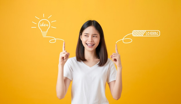 Young smiling asian woman pointing hands to light bulb with text ideas and loading brainstorm on yellow background. Premium Photo