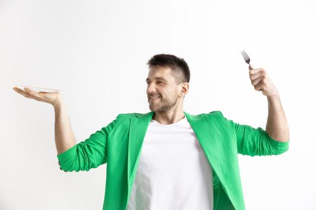 Giovane ragazzo caucasico attraente sorridente che tiene piatto vuoto e forchetta isolato su spazio grigio. copia spazio e simula Foto Gratuite
