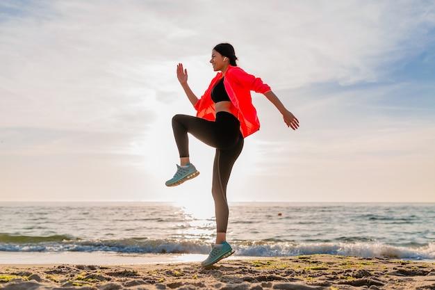 Giovane donna sottile attraente sorridente che fa sport all'alba di mattina che salta sulla spiaggia del mare in abbigliamento sportivo, stile di vita sano, ascolto di musica sugli auricolari, indossa una giacca a vento rosa, divertendosi Foto Gratuite
