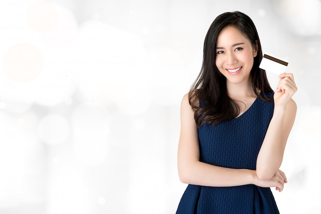 Young smiling beautiful asian woman presenting credit card in hand Premium Photo