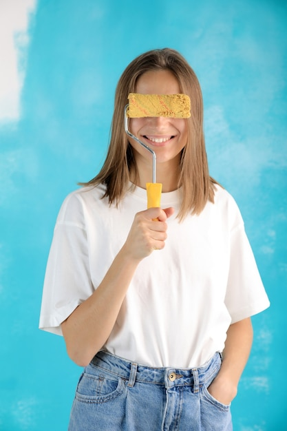 青い背景で隔離の壁画のペイントローラーを保持しているカジュアルな服を着て若い笑顔の美しい女性。 Premium写真