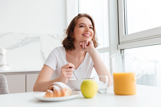 Young smiling brunette woman in white tshirt having healty breakfast while siting at the kitchen table Free Photo