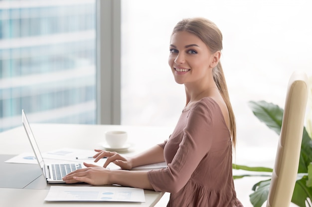Young smiling businesswoman sitting at office desk looking at camera Free Photo