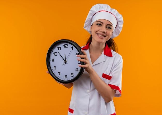 La giovane ragazza caucasica sorridente del cuoco in uniforme del cuoco unico tiene l'orologio isolato sulla parete arancione con lo spazio della copia Foto Gratuite