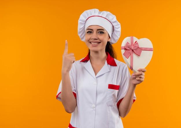 シェフの制服を着た若い笑顔の白人料理人の女の子は、ハート型のボックスを保持し、コピースペースでオレンジ色の壁に孤立して指します 無料写真