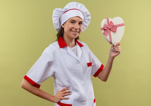 シェフの制服を着た若い笑顔の白人料理人の女の子は、ハート型のボックスを保持し、コピースペースと緑のスペースで隔離の腰に手を置きます 無料写真