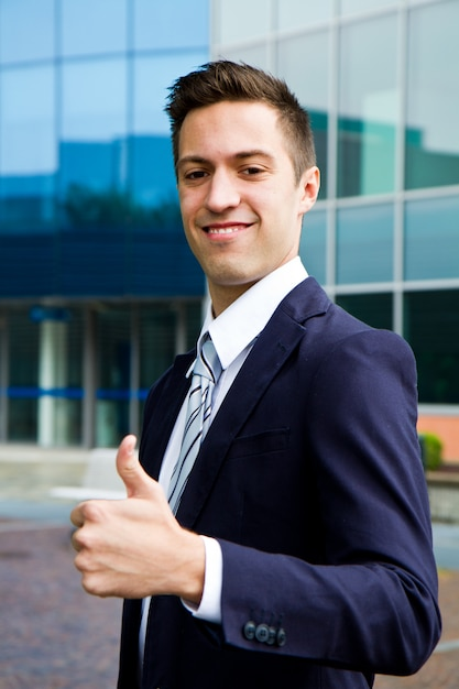 Premium Photo   Young smiling confident man doing thumbs