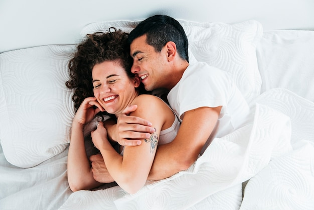 Young smiling couple under duvet on bed Free Photo