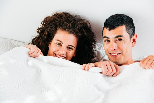 Young smiling couple under duvet Free Photo