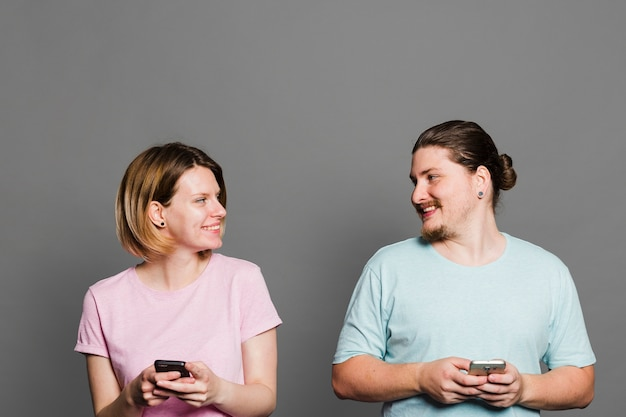 Young smiling couple holding mobile phone in hand against grey wall Free Photo