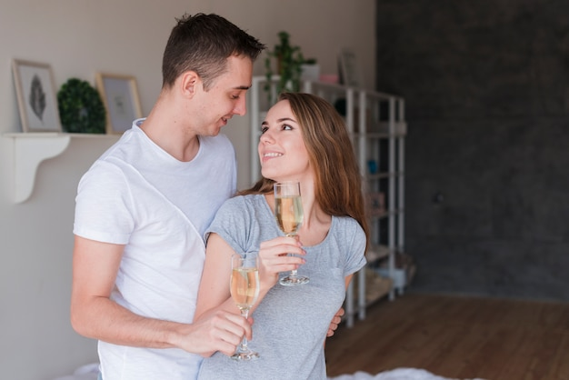 Young smiling couple hugging with glasses at home Free Photo