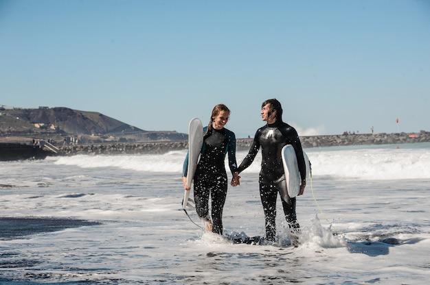 Молодая улыбающаяся пара серферов в черных гидрокостюмах, держащих друг друга за руки и идущих в воде с досками для серфинга Premium Фотографии