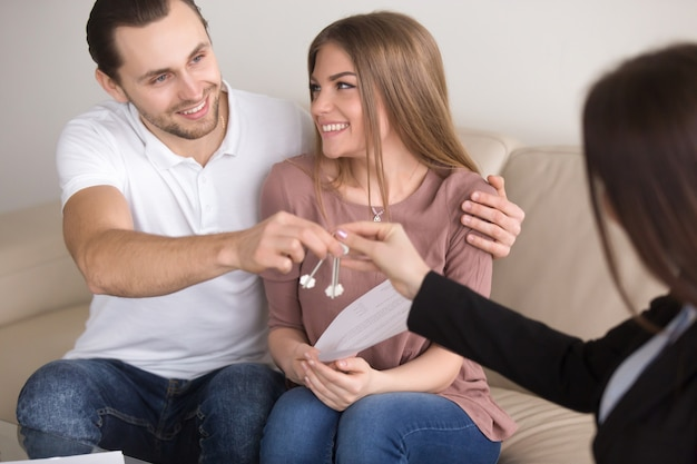 Young smiling couple owners getting keys to own house apartment Free Photo