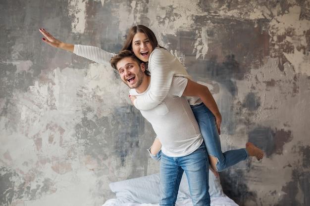 Молодая улыбающаяся пара играет на кровати дома в повседневной одежде, мужчина и женщина веселятся вместе, сумасшедшие положительные эмоции, счастливы, держась за руку Бесплатные Фотографии