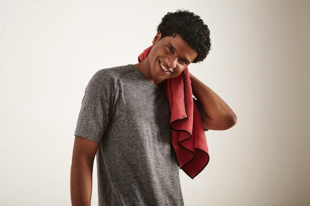 白地に赤いワッフルマイクロファイバータオルで首を拭く灰色のテクニカルtシャツを着て若い笑顔の暗い巻き毛のアフリカ系アメリカ人アスリート 無料写真