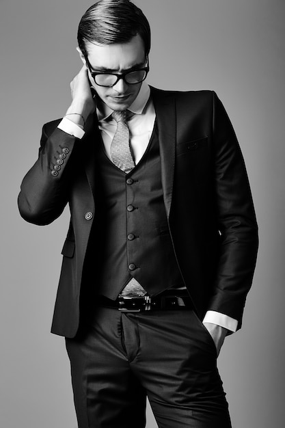 Young smiling elegant handsome  businessman male model in a suit and fashionable glasses, posing in studio Free Photo